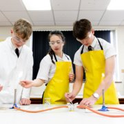 Three Students in Yellow Science Aprons at Bench
