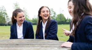 Girls Sitting Around a Bench laughing