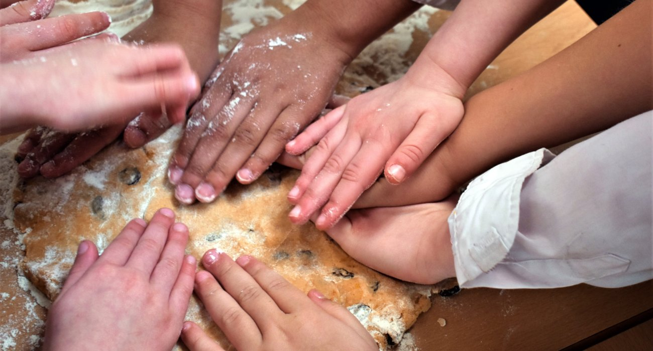 Many Children's Hands Work Together to Knead Cookie Dough