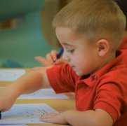 A Little Boy in Nursery Draws with a Fat Blue Crayon