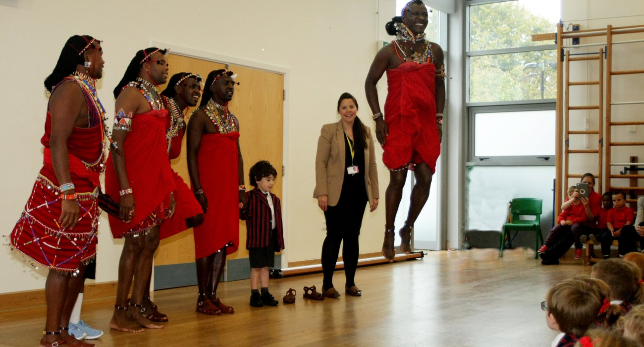 Visiting Ma'asai Warrior Leaping as Reception Pupil and Teacher Look On